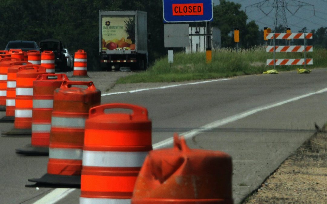 orange construction cones on highway merging traffic to one lane